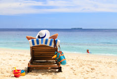 Mutter entspannen sich während Kinderspiel im Wasser am Strand Lizenzfreies Stockfoto