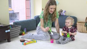 Mutter entwickeln ihre Tochterphantasie, indem sie unsichtbares Lebensmittel vom Spielzeugteller isst stock footage