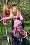 Mutter erlernt Tochter, um mit dem Fahrrad zu fahren Stockfotografie
