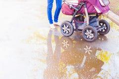 Mutter Erschütterungen an den im Freien ein Kinderwagen Lizenzfreie Stockfotos