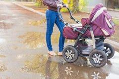 Mutter Erschütterungen an den im Freien ein Kinderwagen Stockfoto