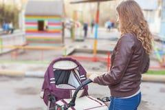 Mutter Erschütterungen an den im Freien ein Kinderwagen Lizenzfreies Stockbild