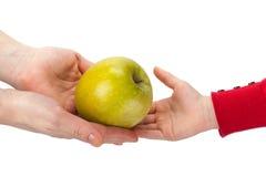 Mutter führt ihrem Kind einen Apfel, das auf Weiß lokalisiert wird Lizenzfreie Stockfotos