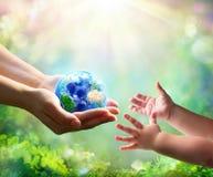 Mutter geben blaue Erde in den Tochter-Händen lizenzfreie stockfotografie