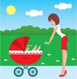 Mutter geht mit dem Kind in einem Wagen Stockfoto