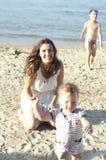 Mutter genießt summerday mit ihrem kida am Strand Lizenzfreie Stockfotos