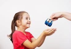 Mutter gibt einem kleinen Mädchen den Geldbeutel Stockfotografie