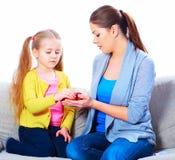 Mutter gibt einem Mädchen einen roten Apfel Stockfoto