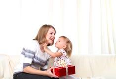 Mutter gibt Geschenk zum dauthter und zum Küssen Lizenzfreie Stockfotos