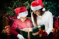 Mutter gibt ihrem Kind eine Weihnachtsgeschenkbox mit hellen Strahlen Lizenzfreies Stockbild