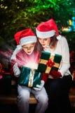 Mutter gibt ihrem Kind eine Weihnachtsgeschenkbox mit hellen Strahlen und Stockbilder