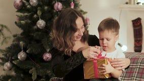 Mutter gibt ihrem kleinen Sohn für das neue Jahr ein Geschenk stock footage