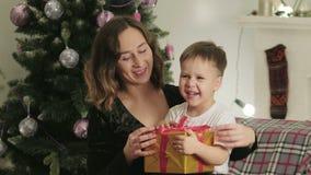 Mutter gibt ihrem kleinen Sohn für das neue Jahr ein Geschenk stock video footage