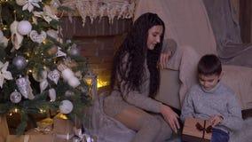 Mutter gibt ihrem Sohn auf Heiliger Nacht einen Kasten mit einem Geschenk stock footage