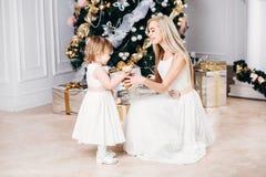 Mutter gibt ihrer Tochter ein Geschenk nahe Stockfotos