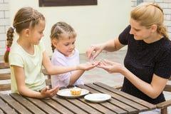 Mutter gießt in Grifftochter-Süßigkeiten Pulver für kleine Kuchen Stockbild
