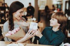 Mutter glücklich mit Sohn Sohn-Geschenk-Blumen und Lächeln Glück-Familie am Tag am 8. März Schöne Mutter-und hübscher Jungen-glüc lizenzfreies stockfoto