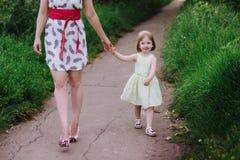 Mutter hält die Hand der Tochter und geht der Weg auf der Natur im Sonnenunterganglicht Lizenzfreie Stockfotografie