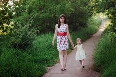 Mutter hält die Hand der Tochter und geht der Weg auf der Natur im Sonnenunterganglicht Stockbild