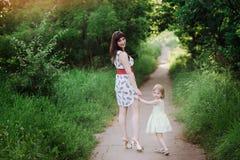Mutter hält die Hand der Tochter und geht der Weg auf der Natur im Sonnenunterganglicht Stockfotos