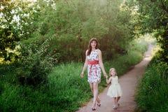 Mutter hält die Hand der Tochter und geht der Weg auf der Natur im Sonnenunterganglicht Lizenzfreies Stockfoto