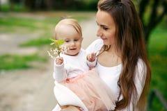 Mutter hält ihre kleine Tochter in ihren Armen unter blühenden Bäumen Mutter und ihr kleines Baby weared Blickkleid der rosa Fami lizenzfreie stockfotografie