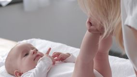 Mutter hält kleine Beine der Tochter dann leicht berührt und küsst sie, das glückliche Baby, das auf ändernder Tabelle liegt stock video footage