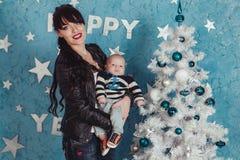Mutter hält neugeborenes Baby in der Seemannstrickjacke am weißen Plastikweihnachtsbaum gegen blauen Wandhintergrund Lizenzfreie Stockbilder