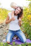Mutter hält Sohn auf Schultern, Herbstzeit Lizenzfreies Stockfoto