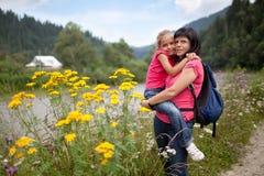 Mutter hält Tochter auf Händen an Stockbild