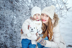 Mutter hält Tochter auf Händen im Winterwald Stockbilder