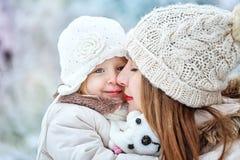 Mutter hält Tochter auf Händen im Winterwald Lizenzfreies Stockfoto