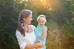 Mutter hält Tochter in ihren Armen und in Spielen auf der Natur Lizenzfreie Stockbilder