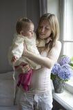 Mutter halten ihr blondes ernstes Baby an Lizenzfreies Stockbild