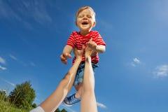 Mutter hebt lachenden Sohn mit den geraden Armen an Stockfoto