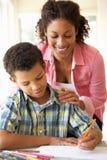 Mutter-helfender Sohn mit Hausarbeit zu Hause Lizenzfreie Stockfotos