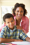 Mutter-helfender Sohn mit Hausarbeit zu Hause Lizenzfreies Stockfoto
