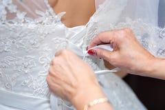 Mutter hilft der Braut, ein Heiratskleid an zu setzen Hände binden ein Korsett eines Heiratskleides, ein Abschluss oben stockbild