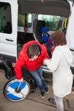 Mutter hilft ihrem behinderten Sohn weg vom Schulbus Lizenzfreies Stockbild