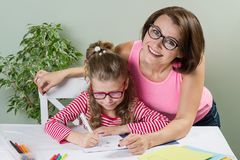 Mutter hilft ihrem Volksschuleschüler der Tochter in ihrem Notizbuch, Lizenzfreies Stockfoto