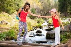 Mutter hilft ihrer Tochter, auf eine Holzbrücke zu gehen Lizenzfreie Stockfotos