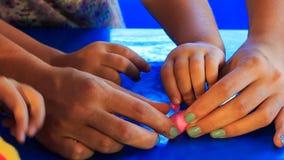 Mutter hilft Kinderskulptur von rosa Plasticine auf blauer Tabelle stock video
