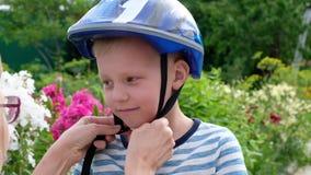 Mutter hilft seinem Sohn setzte an einen Sturzhelm, um ein Fahrrad im Stadtpark sicher zu reiten stock footage