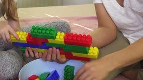 Mutter hilft Tochter, eine Wand von bunten Spielziegelsteinen zu errichten stock footage