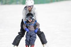 Mutter hilft Tpoddler-Jungen Ski Downhill Sicher angekleidet Stockbilder
