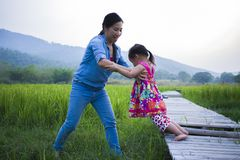 Mutter ihrem Kind helfen, Strom, anhebende Tochter der Mutter zu kreuzen auf dem Reisgebiet stockfoto