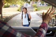 Mutter im Auto, das weg von der Tochter in Front Of School Gates fällt lizenzfreie stockfotografie