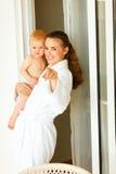 Mutter im Bademantel mit dem Schätzchen, das in Kamera zeigt Lizenzfreie Stockfotos