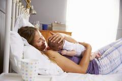 Mutter im Bett, das schlafende neugeborene Baby-Tochter hält Lizenzfreies Stockfoto