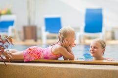 Mutter im Pool und Tochter auf Poolseite haben Spaß und sprechen in tr Lizenzfreies Stockfoto